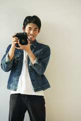 Young man with camera on hands, smiling at camera