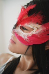 Young woman in feather mask