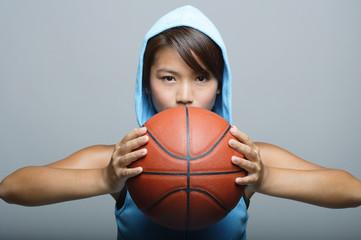 Young woman with basketball looking at camera