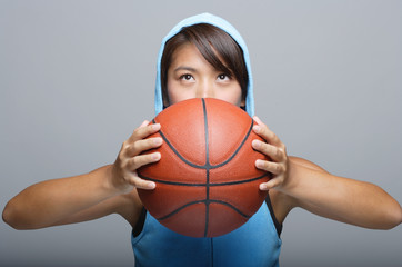 Young woman with basketball looking up