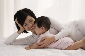 Woman lying on bed with baby girl