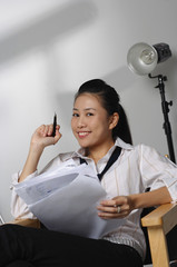 Young woman with paper and pen smiling at camera