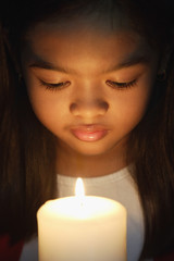 Girl holding and looking at candle