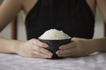 Young woman holding bowl of rice with both hands