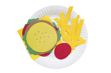 hamburger and french fries from a paper. burger, french fries and ketchup made of colored paper on a disposable plate. the concept of junk food. isolated on white background, top view