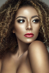Beautiful portrait of afro woman. Young lady posing close up with colorful make up and curly hair.