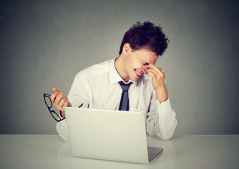 Tired business man rubbing his eye sitting at table with laptop