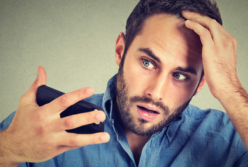 portrait, shocked man feeling head, surprised he is losing hair Wall mural