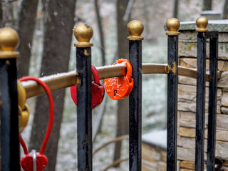 The wedding lock on a fence lattice covered with snow after snowfall