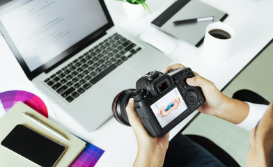 photographer checking dslr camera on desk
