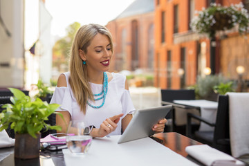 Woman sitting in outdoor cafe and using tablet