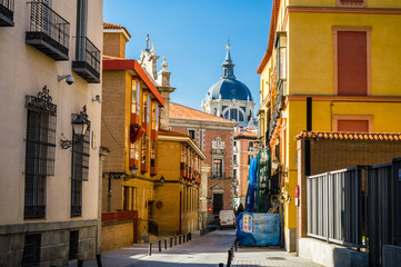 Colorful Madrid street and Almudena Cathedral view in Madrid, Spain