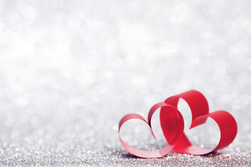 Red ribbon hearts on glitters