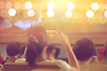 woman using smartphone to take a video at a concert. Modern life