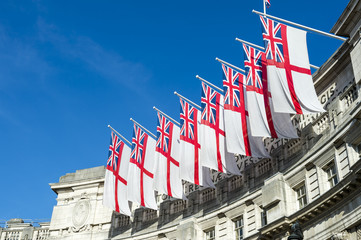 Traditional white ensign flags fly in a row atop Admiralty Arch, the ceremonial gateway between Trafalgar Square and The Mall in London, England, UK
