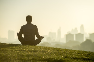 Silhouette of a man sitting in the lotus position meditating on the grassy top of Primrose Hill in front of a misty golden sunrise view of the London city skyline Wall mural