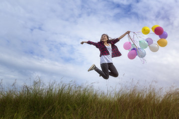 Beautiful girl holding balloons Jumping in prairie grass. On a c