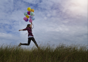 Beautiful girl holding balloons running in prairie grass. On a c