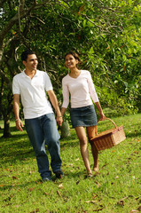 Couple walking in park, woman carrying picnic basket