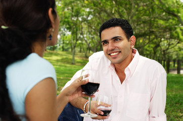 Couple holding wine glasses in park, over the shoulder view