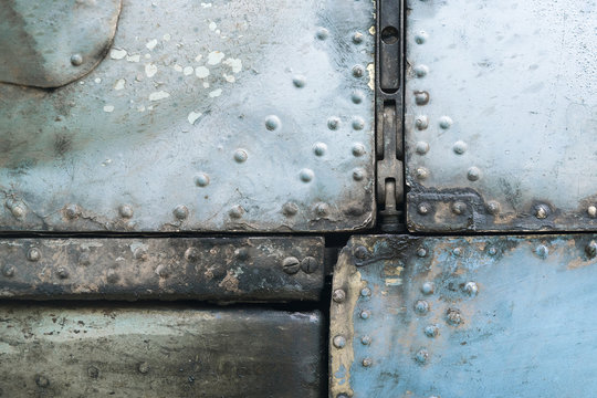 Old blue and silver metal surface of the aircraft fuselage with rivets