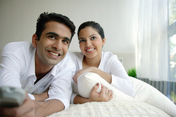 Couple lying on bed, man holding remote control