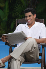 Man sitting in chair by the pool, reading a newspaper