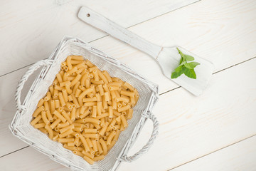 pasta in wicker basket and petals on the wooden spoon on white old wooden boards