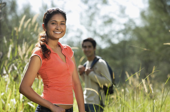 Young couple hiking in the wilderness and smiling at camera