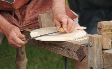 A Classic Craft Worker Shaping a Round Disc of Wood.