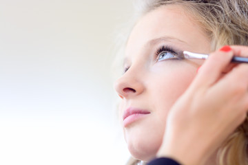 A blond girl in a beauty salon doing make-up.Shallow depth of field.