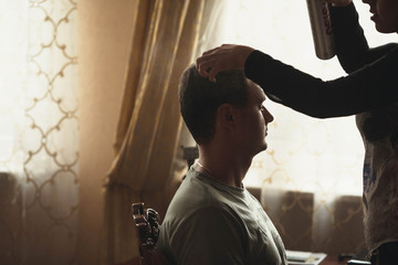 barber makes hairstyle for the young groom