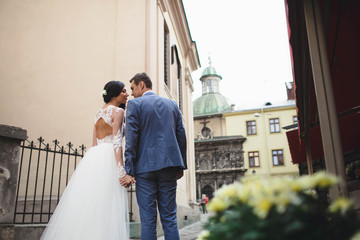groom and his charming wife walking in the large city