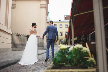 groom and his charming wife walking in the city