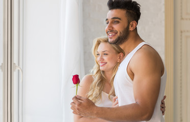 Young Beautiful Couple Stand Near Big Window, Hispanic Man Give Woman Red Rose, Happy Smile Lovers
