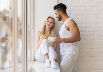 Young Beautiful Couple Stand Near Big Window, Drink Morning Coffee Cup, Happy Smile Hispanic Man And Woman Lovers