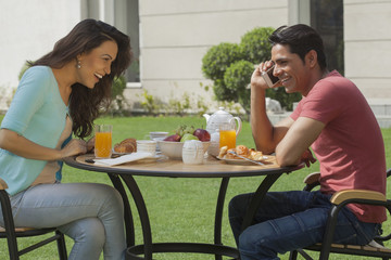 India, Man and woman at breakfast table in garden