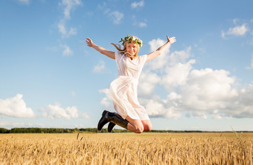 happy woman in wreath jumping on cereal field