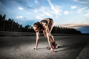 Молодая спортсменка готовится бежать.