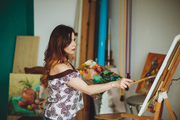 Woman artist painting a picture in a studio