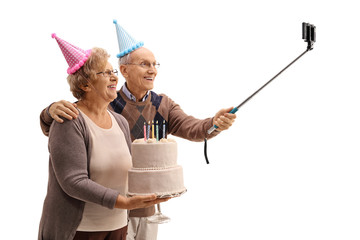 Happy seniors with party hats and a birthday cake taking a selfi