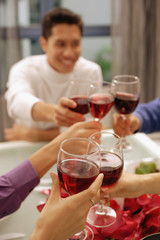 Friends toasting with wine glasses across dinner table