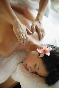 Young woman receiving back massage, eyes closed