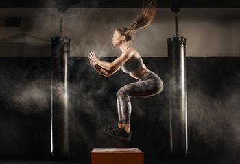 sporty girl jumping over some boxes in a cross-training gym