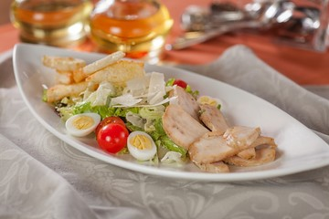Delicious Caesar salad with chicken meat and cheese on a white plate