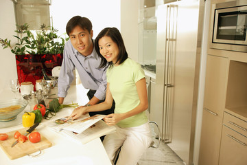 Couple in kitchen with cookbook, looking at camera