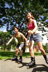 Couple inline skating at park