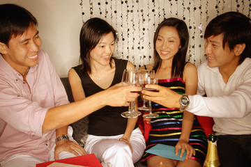 Couples sitting down raising wine glasses, toasting