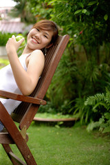 Young woman sitting on chair, outdoors.