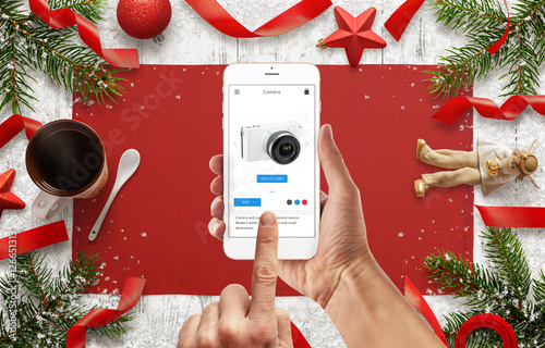 Online shopping with mobile phone. Christmas decorations on white wooden table.
